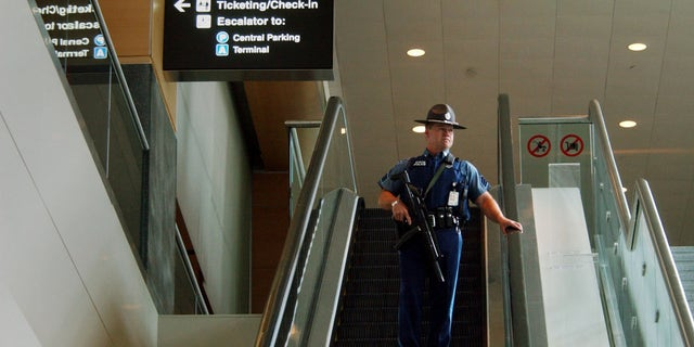 BOSTON - AUGUST 10:  A Massachusetts State Police officer rides an escalator at Logan International Airport August 10, 2006 in Boston, Massachusetts. The Department of Homeland Security raised the terrorism alert to Red, the highest level, for commercial flights from Britain to the United States after an alleged terrorist plot to blow up planes was disrupted by British authorities.  (Photo by Darren McCollester/Getty Images)
