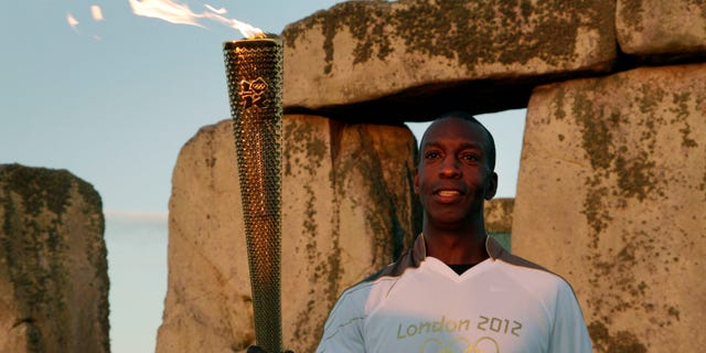 July 12, 2012: U.S. Olympian sprinter Michael Johnson poses for photographers holding the Olympic Flame at Stonehenge, England.