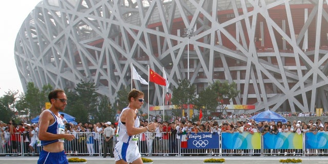 FILE - the Aug. 22, 2008 file photo shows Italy's Alex Schwazer, right, leading Yohan Diniz of France on his way to winning the gold medal in the men's 50-kilometer walk during the athletics competitions near the National Stadium at the Beijing 2008 Olympics in Beijing. Italian Olympic team said Monday, Aug. 6, 2012 that defending 50k walk champion Alex Schwazer tested positive for doping. (AP Photo/Itsuo Inoue)