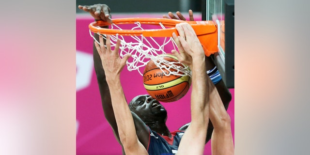 Britain's Pops Mensah-Bonsu tries unsuccessfully to block a dunk by Russia's Andrei Kirilenko during a men's basketball game at the 2012 Summer Olympics, Sunday, July 29, 2012, in London. (AP Photo/Charles Krupa)