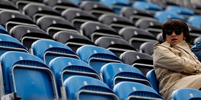 A spectator sits next to a section of empty seats during the equestrian eventing dressage phase at the 2012 Summer Olympics, Sunday, July 29, 2012, in London. (AP Photo/David Goldman)