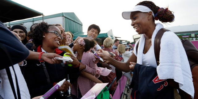 July 31, 2012: Venus Williams of the United States signs autographs after a doubles match at the All England Lawn Tennis Club in Wimbledon, London at the 2012 Summer Olympics.
