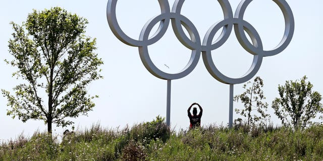 Volunteer Abby Idowu, of London, stretches under the Olympic rings while being photographed by friends on the other side of a hill at Olympic Park prior to the 2012 Summer Olympics, Thursday, July 26, 2012, in London. The opening ceremonies for the games will be held Friday, July 27. (AP Photo/Charles Krupa)