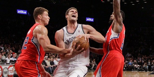 Los Angeles Clippers forward Blake Griffin, left,gets his hand on the ball as Brooklyn Nets center Brook Lopez, center, drives toward the basket with Clippers center DeAndre Jordan (6) also defending in the second half of an NBA basketball game at the Barclays Center, Thursday, Dec. 12, 2013, in New York. The Nets won 102-93. (AP Photo/Kathy Willens)