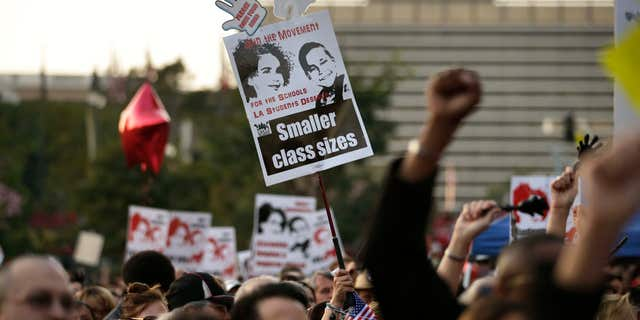 Feb. 26, 2015: People hold up signs and chant their slogans as thousands of teachers gather for a rally to demand higher wages and smaller class sizes