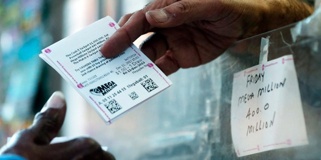A person buys a Mega Millions lottery tickets at a newsstand in Philadelphia. No one matched all six numbers in Friday night's drawing.