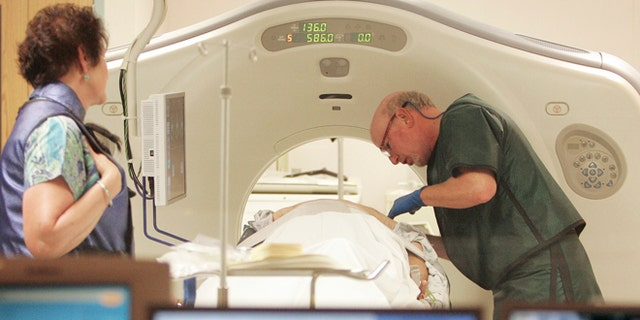 FILE - In this June 3, 2010, file photo, Dr. Steven Birnbaum works with a patient in a CT scanner at Southern New Hampshire Medical Center in Nashua, N.H. A national study suggests the world's top cancer killer isn't always as deadly as doctors once thought, finding that more than 18 percent of lung cancers detected in screening scans are likely so slow growing that theyâd never cause problems. But the provocative results are unlikely to change how doctors treat lung cancer. (AP Photo/Jim Cole, File)