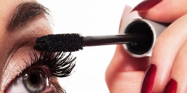 Woman eye with long eyelashes and mascara brush