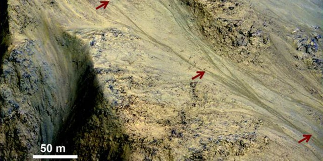 Features called recurring slope lineae (RSL), which could indicate seasonal flows of salty water, are found on some Martian slopes in warmer months. Red arrows point out an RSL in this image taken by the High Resolution Imaging Science Experime