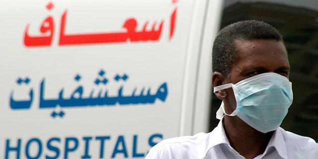 A man, wearing a surgical mask as a precautionary measure against the novel coronavirus, walks near a hospital in Khobar city in Dammam.