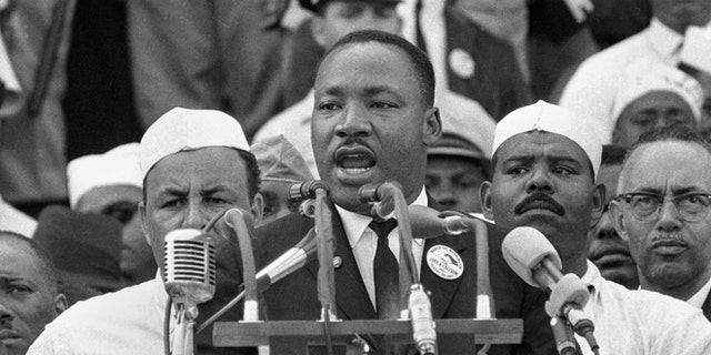 """FILE- In this Aug. 28, 1963, black-and-white file photo Dr. Martin Luther King Jr., head of the Southern Christian Leadership Conference, addresses marchers during his """"I Have a Dream"""" speech at the Lincoln Memorial in Washington. (AP Photo/File)"""