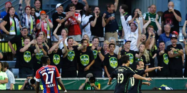 Los Angeles Galaxy forward Landon Donovan, right, celebrates with Chivas USA forward Erick Torres (19) as Bayern Munich's David Alaba (27) watches, after Donovan scored the go-ahead goal in the second half of the MLS All-Star soccer game, Wednesday, Aug. 6, 2014, in Portland, Ore. The MLS All-Stars won 2-1. (AP Photo/Ted S. Warren)