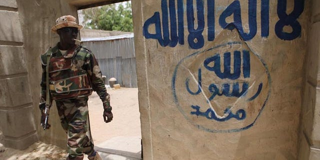 A Nigerien soldier walks out of a house that residents say a Boko Haram militant had forcefully seized and occupied in Damasak March 24, 2015. Boko Haram militants have kidnapped more than 400 women and children from the northern Nigerian town of Damasak that was freed this month by troops from Niger and Chad, residents said on Tuesday. Nigerian, Chadian and Niger forces have driven militants out of a string of towns in simultaneous offensives over the past month.   REUTERS/Joe Penney - RTR4UPRZ