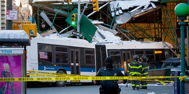 A Metropolitan Transportation Authority bus rests against scaffolding at 14th Street and 7th Avenue in New York, Wednesday, Feb. 12, 2014, after an early morning collision between the bus and a truck. One person was killed and at least four were injured in the crash, that also involved several parked vehicles. (AP Photo/Craig Ruttle)