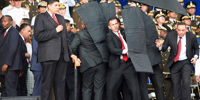 Security personnel surround President Maduro