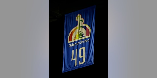 A banner printed with the names of the Pulse nightclub shooting victims and 49, the number of people who died in the shooting, is unveiled in the Amway Center during a tribute prior to an NBA basketball game between the Orlando Magic and the Miami Heat, Wednesday, Oct. 26, 2016, in Orlando, Fla. (AP Photo/John Raoux)
