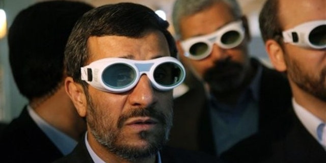 File: Iranian President Mahmoud Ahmadinejad, wears eye protection goggles as he visits an exhibition of Iran's laser science in Tehran.