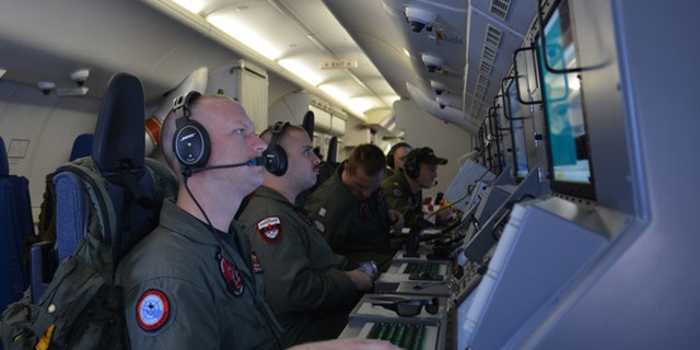 In this photo provided by the U.S. Navy, crew members on board an aircraft P-8A Poseidon assist in search and rescue operations for Malaysia Airlines flight MH370 in the Indian Ocean on Sunday, March 16, 2014. Malaysian authorities on Sunday examined a flight simulator that was confiscated from the home of one of the missing jetliner's pilots. The Boeing 777 went missing less than an hour into a March 8, flight from Kuala Lumpur to Beijing as it entered Vietnamese airspace. (AP Photo/U.S. Navy, Eric A. Pastor)