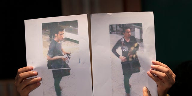 Pictures of the two men, a 19-year old Iranian, identified by Malaysian police as Pouria Nour Mohammad Mehrdad, left, and the man on the right, his identity still not released, who boarded the now missing Malaysia Airlines jet MH370 with stolen passports, is held up by a Malaysian policewoman during a press conference, Tuesday, March 11, 2014 in Sepang, Malaysia. One of the two men traveling on a missing Malaysian Airlines jetliner was an Iranian asylum seeker, officials said Tuesday, as baffled authorities expanded their search for the Boeing 777 on the opposite side of the country from where it disappeared nearly four days ago with 239 people on board.(AP Photo/Wong Maye-E)