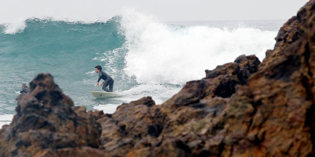 A surfer rides a wave by Point Dume in Malibu, California. Starting Wednesday, students at Malibu High School will be relocated from a campus building that teachers suspect has caused incidents of cancer  (REUTERS/Mario Anzuoni)