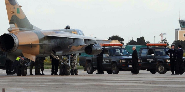 One of two Libyan Air Force Mirage jet fighters to land in Malta, is surrounded by Maltese police after it landed in Malta's International airport, Monday, Feb. 21, 2011.