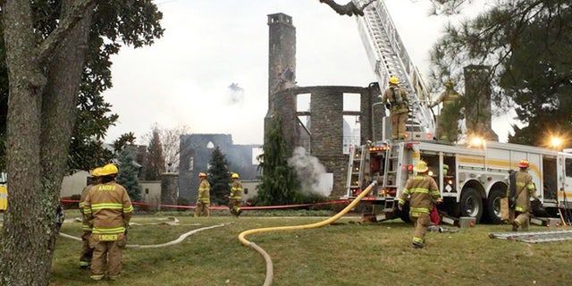 Firefights work to put out a fire at a home on Childs Point Road, Monday, Jan. 19, 2015, in Annapolis, Md. Six people, at first thought to be out of town, were unaccounted for Monday night after the fire that gutted the seven bedroom, 7 1/2 bath home. (AP Photo/The Baltimore Sun, Tim Pratt)
