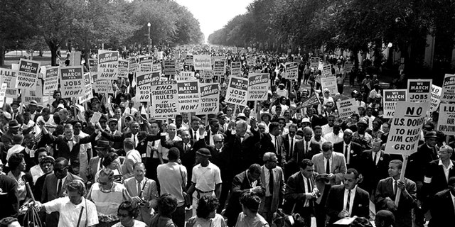 In this Aug. 28, 1963, file photo Dr. Martin Luther King Jr., center left with arms raised, marches along Constitution Avenue with other civil rights protesters carrying placards, from the Washington Monument to the Lincoln Memorial during the March on Washington. (AP Photo, File)