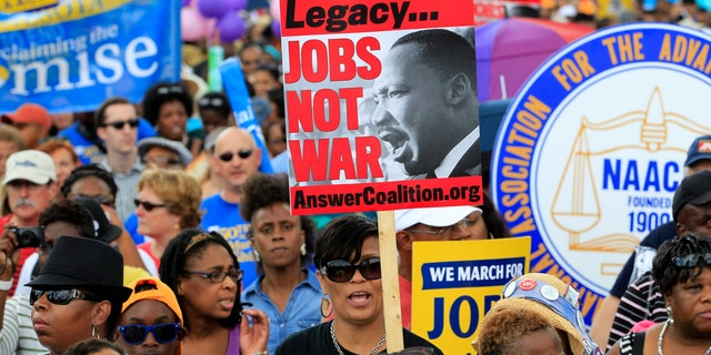 Demonstrators march towards the Martin Luther King Junior Memorial during the rally to commemorate the 50th anniversary of the 1963 March on Washington Saturday, Aug. 24, 2013, in Washington.