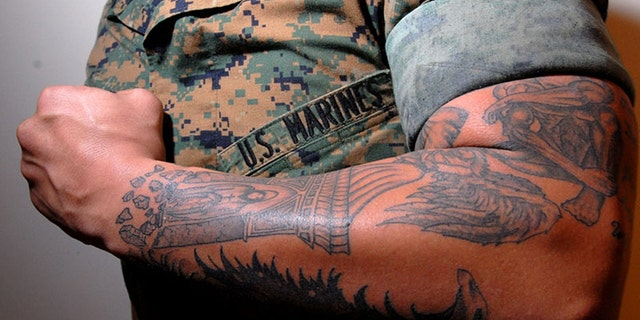 """Lance Cpl. Tom Blachard showing his tattoo """"sleeves"""" that cover one of his arms. The Marines have just eased up on their tattoo rules."""