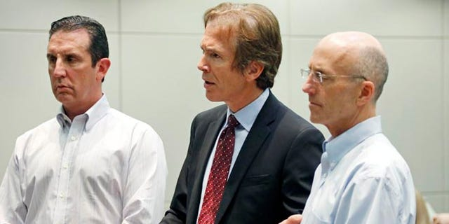 In this May 22, 2014 photograph, Mark Mayfield, right, a member of the board of the Central Mississippi Tea Party, and attorney John Reeves, left, listen as Mayfield's attorney Merrida Coxwell, center, responds to questions from city Judge Dale Danks in Madison, Miss., city court, during an initial court appearance.