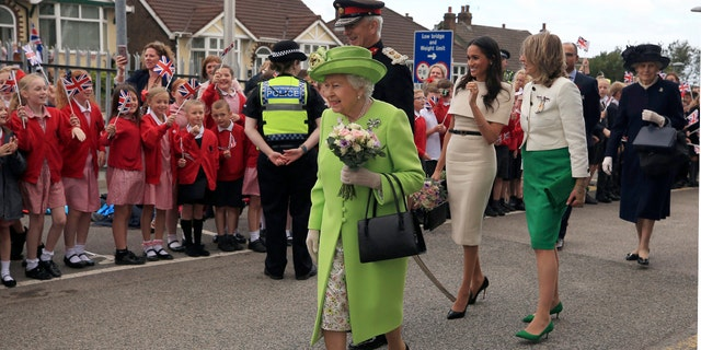 Britain's Queen Elizabeth II and Meghan, the Duchess of Sussex, third right, are welcomed by well-wishers after arriving by Royal Train at Runcorn Station, northwest England.
