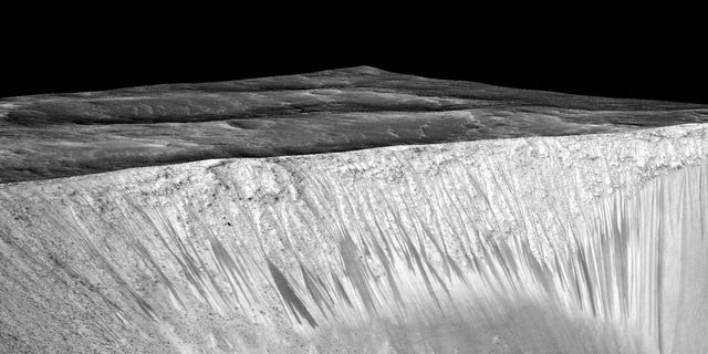Dark narrow streaks called recurring slope lineae emanating out of the walls of Garni crater on Mars.
