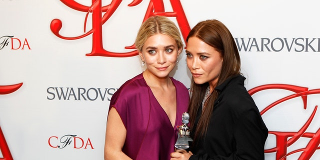 Designers Ashley (L) and Mary-Kate Olsen smile backstage with their award for Womenswear Designer of the Year at the 2012 Council of Fashion Designers of America (CFDA) Fashion Awards in New York June 4, 2012.