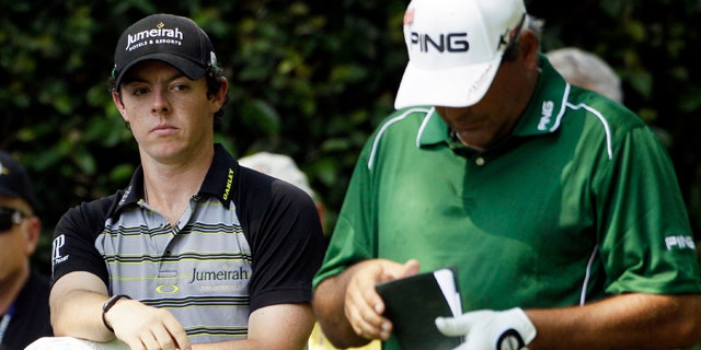 April 10, 2011: Rory McIlroy, left, of Northern Ireland looks over at Angel Cabrera of Argentina as he checks his course notes during the final round of the Masters golf tournament.