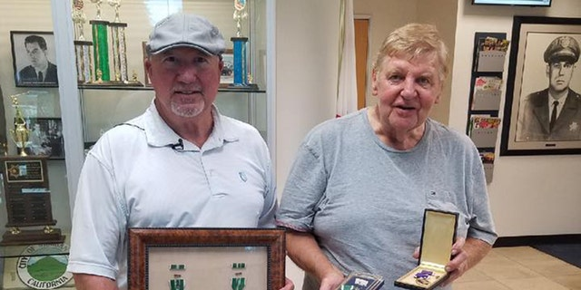 Lenny Kurtz and Jeffrey Simon pose with their war medals after Simon was reunited with his lost Purple Heart.