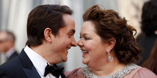 """Melissa McCarthy, best supporting actress nominee for her role in """"Bridesmaids,"""" and her husband, Ben Falcone, arrive at the 84th Academy Awards in Hollywood, California, February 26, 2012.  REUTERS/Lucy Nicholson  (UNITED STATES) (OSCARS-ARRIVALS)"""