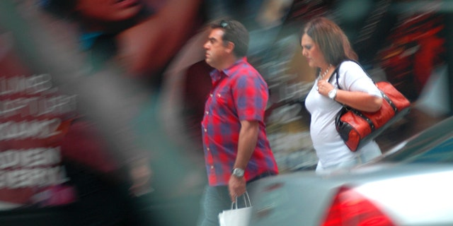 In this August 2013 surveillance photo provided by the Drug Enforcement Administration, Francisco Salgado and his sister Alejandra walk on New York's Third Avenue in midtown Manhattan where authorities say they made multiple cash deposits at banks within a few blocks of each other as part of a Mexican cartel money-laundering scheme. Authorities say the pair entered seven different banks making cash deposits of just under $10,000, all from piles of drug money they were carrying in designer purses and shopping bags. (DEA via AP)