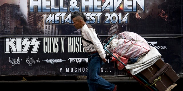"""A man pulls a dolly loaded with supplies past publicity of  """"Hell and Heaven Metal Fest"""" concert, posted on bus in Mexico City, Friday March 7, 2014. The Mexico state government canceled the concert saying the March 15-16 """"Hell and Heaven Metal Fest"""" planned for a fairground just east of Mexico City did not have adequate safety plans, posing a risk to concert-goers. (AP Photo/Eduardo Verdugo)"""