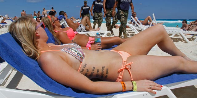 In this March 15, 2012 file photo, navy sailors patrol as people sun bathe on the beach during spring break in Cancun, Mexico.