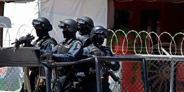 """In this picture taken Tuesday May 17, 2011, Mexican federal police stand outside the Goodbar Old West saloon, allegedly owned by Bernabe Monje Silva, in Durango, Mexico. Federal authorities claim that the March 27 arrest of Monje Silva, alias """"M-14,"""" led to the discovery of 219 bodies found in at least seven mass clandestine graves. (AP Photo/Dario Lopez-Mills)"""