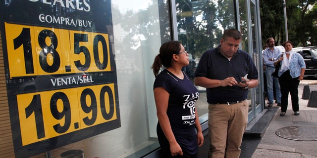 People stand outside an exchange house advertising the sale of U.S. dollars at the rate of 19.90 Mexican pesos per dollar in Mexico City, Monday, Sept. 19, 2016. The Mexican currency reached the psychological barrier of 20 pesos per dollar, and analysts and commentators cited the role of the U.S. presidential campaign. (Photo AP Photo / Marco Ugarte)