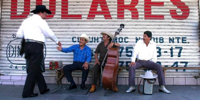 """FILE - In this June 25, 2002 file photo, Northern Mexican musicians who play """"Norteno"""" music greet each other as they wait for clients under a sign that reads """"dollars"""" in Spanish in Monterrey, Mexico. Mexico's central bank says remittances sent home by Mexicans living abroad rebounded in 2014 after falling the previous year. Money sent home by Mexicans are one of the country's main sources of foreign income, along with oil exports. (AP Photo/Gregory Bull, File)"""
