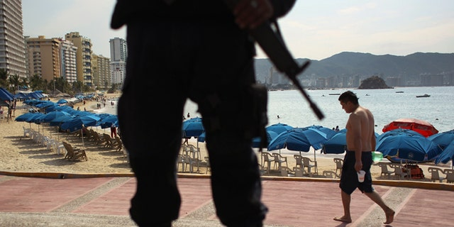 ACAPULCO, MEXICO - MARCH 04:  A Mexican federal policeman stands guard near the beach on March 4, 2012 in Acapulco, Mexico. Drug violence has surged in the coastal resort in the last year, making Acapulco the second most deadly city in Mexico after Juarez. One of Mexico's top tourist destinations, Acapulco has suffered a drop in business, especially from foreign tourists, due to the violence. Toursim accounts for about 70 percent of the economy of Acapulco's state of Guerrero and 9 percent of Mexico's economy.  (Photo by John Moore/Getty Images)