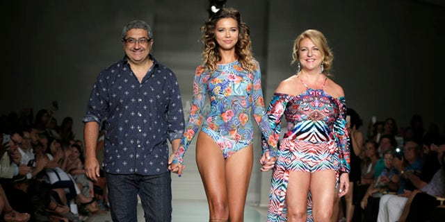 "A model walks down the runway with designers Augusto Hanimian, left, and Lourdes ""Luli"" Hanimian during the Luli Fama swimwear show, Saturday, July 16, 2016, in Miami Beach, Fla. (AP Photo/Lynne Sladky)"