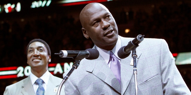 Former Bulls star Michael Jordan (R) talks to the crowd while Scottie Pippen looks on during a ceremony to honor the 20th anniversary of their first world championship at half time of the NBA basketball game between the Utah Jazz and Chicago Bulls in Chicago, Illinois March 12, 2011.