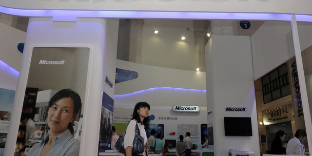 A visitor walks past a Microsoft booth at a computer software expo in Beijing, June 2, 2010.
