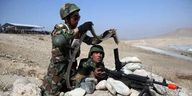 October 22, 2014: Afghan National Army soldiers load their belt-fed machine gun during a mock attack on an enemy's stronghold during a military training exercise at Kabul Military Training Center. (AP Photo/Massoud Hossaini)