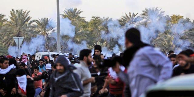 DEc. 23, 2011: Anti-government protesters run as riot police begin firing tear gas.