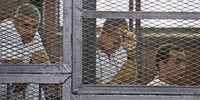 May 15, 2014: In this file photo, from left, Mohammed Fahmy, Canadian-Egyptian acting bureau chief of Al-Jazeera, Australian correspondent Peter Greste, and Egyptian producer Baher Mohamed appear in a defendant's cage along with several other defendants during their trial on terror charges at a courtroom in Cairo. (AP)