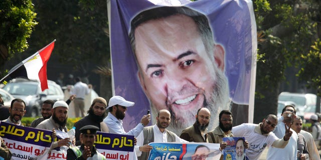March 30, 2012: Supporters of Egyptian presidential candidate Hazem Salah Abu Ismail, a prominent Salafi, celebrate in front of a giant campaign banner at the Higher Presidential Elections Commission, in Cairo, Egypt.